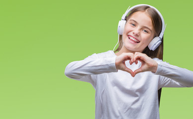 Young beautiful girl wearing headphones listening to music over isolated background smiling in love showing heart symbol and shape with hands. Romantic concept.