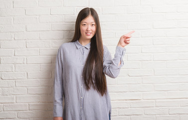 Young Chinese woman over brick wall very happy pointing with hand and finger to the side