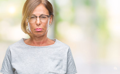 Middle age senior hispanic woman wearing glasses over isolated background depressed and worry for distress, crying angry and afraid. Sad expression.