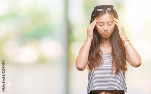 00b9fe1c151 Young asian woman wearing sunglasses over isolated background with hand on  head for pain in head
