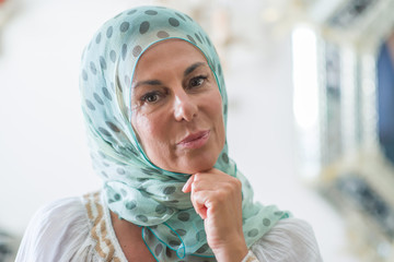 Middle age brunette arabian woman wearing colorful hijab serious face thinking about question, very confused idea