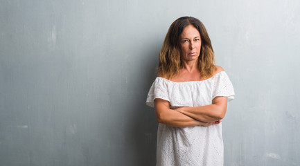 Middle age hispanic woman standing over grey grunge wall skeptic and nervous, disapproving expression on face with crossed arms. Negative person.