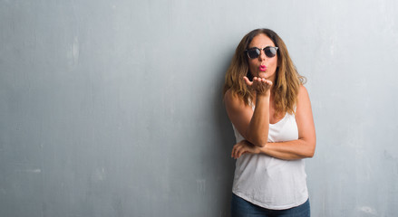 Middle age hispanic woman over grey wall wearing sunglasses looking at the camera blowing a kiss with hand on air being lovely and sexy. Love expression.