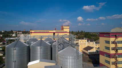 Agricultural Silo. Storage and drying of grains, wheat, corn, soy, against the blue sky with clouds.