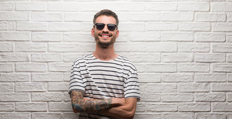 Young adult man wearing sunglasses standing over white brick wall happy face smiling with crossed arms looking at the camera. Positive person.