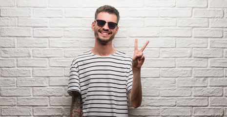 Young adult man wearing sunglasses standing over white brick wall smiling with happy face winking at the camera doing victory sign. Number two.
