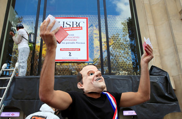 A man wears a mask of France's President Emmanuel Macron as Anti-Globalization movement Attac activists protest in front of HSBC bank during an action to mark the 10th anniversary of the global financial crisis of 2008, in Paris
