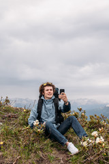 cheerful backpacker is shootting the video while sitting on the hill with wonderful landscape. gadget and technology concept
