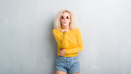 Young blonde woman with curly hair over grunge grey background looking at the camera blowing a kiss with hand on air being lovely and sexy. Love expression.