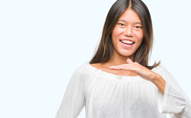 Young asian woman over isolated background gesturing with hands showing big and large size sign, measure symbol. Smiling looking at the camera. Measuring concept.