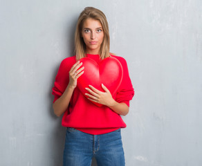 Beautiful young woman over grunge grey wall holding red heart with a confident expression on smart face thinking serious