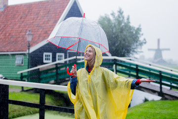 Young girl in rain suit with umbrella stay on bridge with dutch house on background. Netherlands