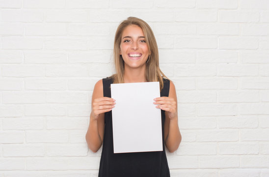Beautiful young woman over white brick wall holding blank paper sheet with a happy face standing and smiling with a confident smile showing teeth