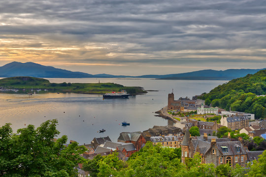 A moody view from a hill in the port town of Oban, Scotland looking out on the town and the water with the Isle of Mull in the distance with a hint of the summer sunset and grey clouds
