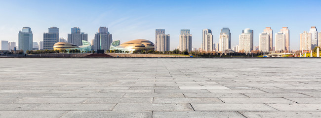 cityscape and skyline of zhengzhou in China from empty brick floor in the daytime