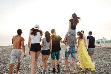 rear view of excited young friends walking on beach. Multiracial group of friends enjoying day at beach