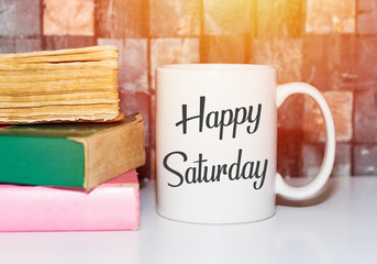 Happy saturday word on white morning coffee cup and books