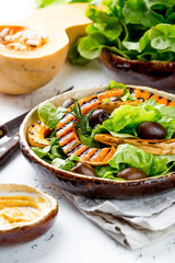Grilled pumpkin and lettuce salad. White background