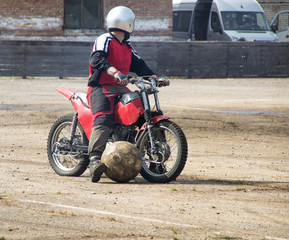 Motoball, man rides a motorcycle and drives a ball with him, close-up, ball