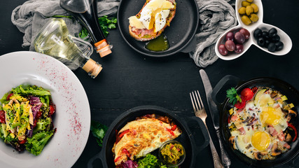 A set of food. Shakshuka, omelette, avocado salad, sandwich with poached egg. On a wooden background. Free space for text. Top view.