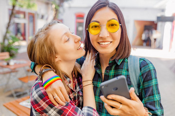 lifestyle selfie portrait of two young positive hipster woman having fun and making selfie