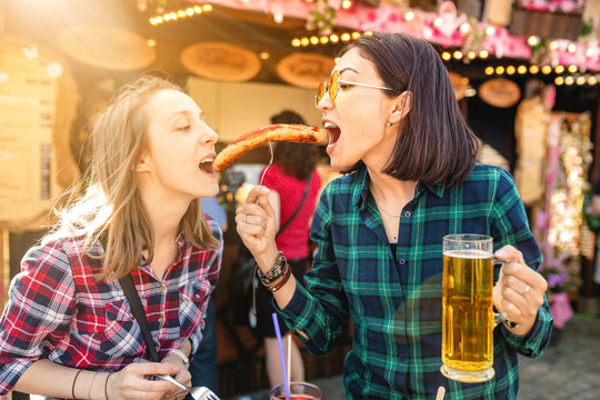 Two girls friends having fun and eating fried sausage and drinks mug of beer at the fair market square in Germany, beer and local food festival concept