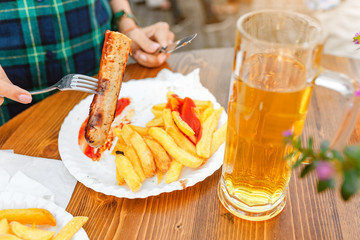 Curry wurst Sausages with beer on the table in outdoor restaurant