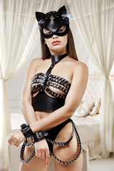 the girl in the black mask. leather belts. woman in the bedroom.