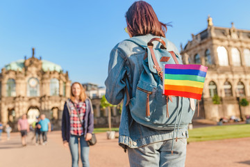 Two girls travelers having fun in Dresden with rainbow flag symbol. Free love relationship concept