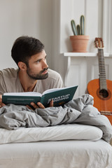Vertical shot of bearded guy with pensive expression, lies on bed, reads business book, learns how increse sales and netprofit, being dep in thoughts. People, spare time and literacy concept
