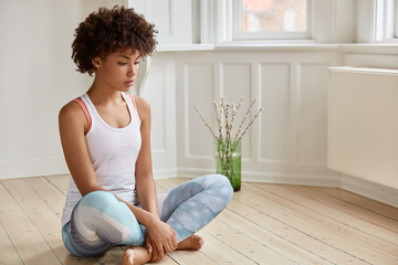 Photo of thoughtful ethnic girl sits in lotus pose on floor, wears casual vest and leggings, tries to relax or concentrate, being at home in spacious light room. Relaxation and lifestyle concept