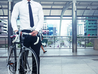 Business man and bicycle walking on street and building background.