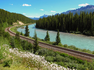 Canadian Pacific Railway train track along the turquoise river in a beautiful nature setting, British Columbia, Canada