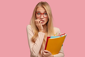 Waist up shot of anxious blonde woman with light hair, bites finger nails, looks nervously at camera, wears spectacles, uses literature for learning material, stands indoor. Emotions before exam