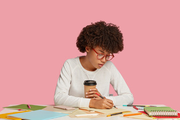 Focused creative multiplier or illustrator uses crayons for making picture, dressed in casual outfit, wears transparent glasses, drinks hot beverage, sits at workplace, poses against pink background