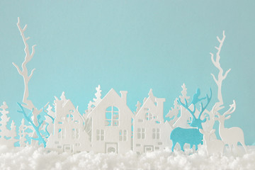 Magical Christmas paper cut winter background landscape with houses, trees, deer and snow in front of pastel blue background.