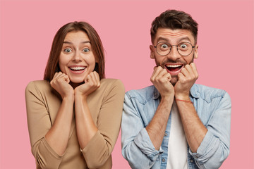 Shot of glad young brother and sister keep hands under chin, have broad smiles, rejoice good news, dressed in casual clothes, isolated over pink background, express happiness. Wow, thats great!