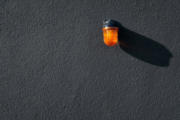 Orange Signalleuchte auf schwarzer Wand