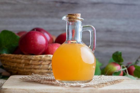 A bottle of apple cider vinegar with fresh apples
