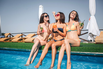 Well-build and excited models sit at edge of swimming pool. They hold cocktails in hands. Young women look to different sides. Their legs are in water.