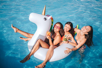 Attractive models are in swimming pool. They have cocktails in hands. Two models sit on float. Third one swimming behind them. They smile and have fun.