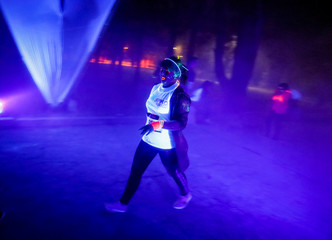 A participants walks as she is sprayed with coloured fluorescent powder during the YARKOcross Night Edition colour run race in Almaty