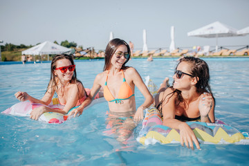 Happy models are in swimming pool. They pose on camera. Two models are lying on floats and look at woman in middle. She stands in water and smile.