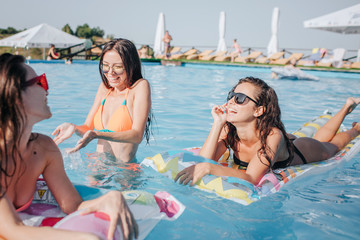 Models in bikini swimming on floats and standing in water in pool. Woman in middle splashing water with hands. Other two models are getting sun tan and enjoying. They smile.
