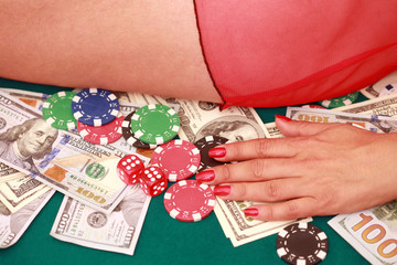 close up of dice in woman's hand with cash and chips at green casino table