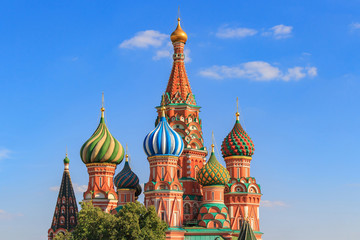 Onion domes of St. Basil's Cathedral in Moscow against blue sky on a sunny summer evening