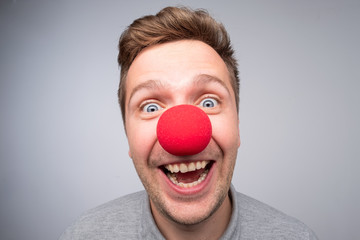 Caucasian man with crazy look wearing a clown nose