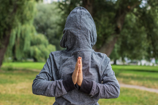 creative prayer pose by human hands concept shot with backwards clothes gray hoodie on body and face behind hood on natural unfocused bokeh effect background and empty copy space for your text