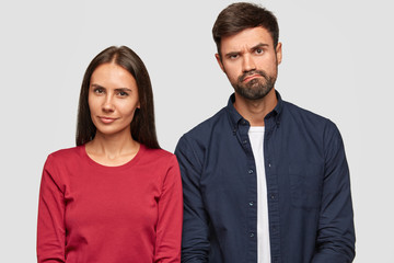 Suspicious beautiful young woman and puzzled unshaven guy stand together against white background, express different emotions, listen some information from interlocutor. Companioship concept.
