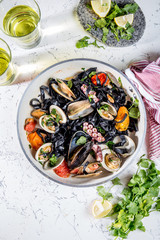 Homemade seafood Black pasta spaghetti with clams mussels octopus vongole in pan with white wine on marbled background